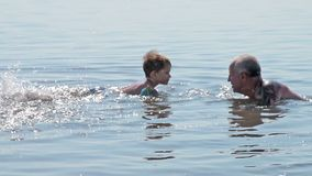 Grandfather and grandson bathing in salty lake