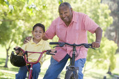 Grandfather and grandson on bikes outdoors smiling Stock Photography