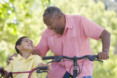 Grandfather and grandson on bikes outdoors smiling Royalty Free Stock Photos