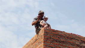 Grandfather and grandson builders. Happy grandfather with his grandson sitting on the brick wall of a new house and my grandfather shows his hand stock video
