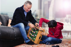 Grandfather and grandson building foosball toy Royalty Free Stock Photo