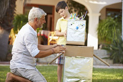 Grandfather And Grandson Building Model Robot In Garden Stock Images