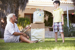 Grandfather And Grandson Building Model Robot In Garden Royalty Free Stock Image