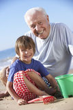 Grandfather And Grandson Building Sandcastle On Beach Stock Photography
