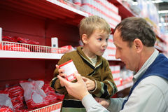 Grandfather and grandson choose conserve. In food shop Stock Photo