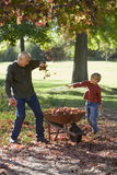 Grandfather and grandson (7-9) collecting autumn leaves in garden, boy throwing leaves at man, smiling Stock Photo