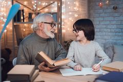 Grandfather and grandson are doing homework at night at home. Granddad is helping boy. stock image