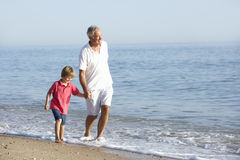 Grandfather And Grandson Enjoying Walk Along Beach Royalty Free Stock Photos