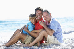Grandfather With Grandson And Father Embracing On Beach Holiday Stock Image