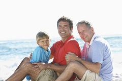 Grandfather With Grandson And Father Embracing On Beach Holiday Stock Photography