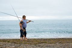 Grandfather and grandson fishing Stock Images