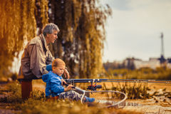 Grandfather with a  grandson on fishing. Royalty Free Stock Images