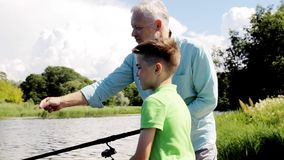 Grandfather and grandson fishing on river berth 3