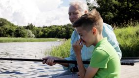 Grandfather and grandson fishing on river berth 9 stock video
