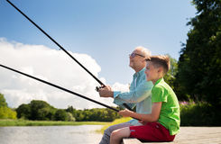 Grandfather and grandson fishing on river berth Stock Photos
