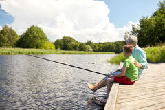 Grandfather and grandson fishing on river berth Royalty Free Stock Photo