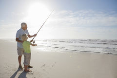 Grandfather and grandson with fishing rod on sunny beach Stock Photo