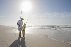 Grandfather and grandson with fishing rods on sunny beach Royalty Free Stock Images