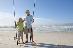 Grandfather and grandson with fishing rods on sunny beach Stock Photos