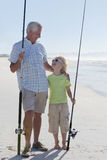 Grandfather and grandson with fishing rods on sunny beach Stock Photo