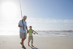 Grandfather and grandson with fishing rods on sunny beach Stock Images