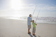 Grandfather and grandson fishing on sunny beach Stock Photography