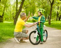 Grandfather and grandson give high five while cycling in the park royalty free stock photos