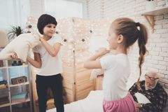 Grandfather, grandson and granddaughter at home. Children are pillowfighting while grandpa is sleeping. royalty free stock image
