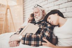 Grandfather, grandson and granddaughter at home. Grandpa and children are sleeping while reading book. Grandfather, grandson and granddaughter at home. Grandpa Royalty Free Stock Image