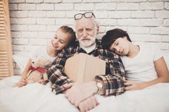 Grandfather, grandson and granddaughter at home. Grandpa and children are sleeping while reading book. Grandfather, grandson and granddaughter at home. Grandpa Stock Photos
