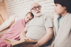 Grandfather, grandson and granddaughter at home. Grandpa is reading book to children. Grandfather, grandson and granddaughter on sofa at home. Grandpa is Royalty Free Stock Images