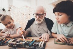 Grandfather, grandson and granddaughter at home. Grandpa teaches children how to braze. royalty free stock images