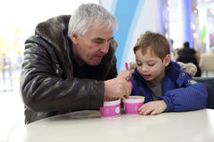 Grandfather and grandson have ice cream Stock Photo