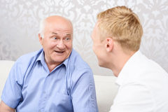 Grandfather and grandson having conversation. Sweet conversation. Portrait of grandfather and grandson sitting and expressive talking to each other Royalty Free Stock Photography