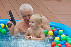 Grandfather and grandson having fun in the pool. Grandfather and grandson relaxing in swimming pool, with colorful balls. Lifestyle family picture Stock Images