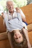 Grandfather And Grandson Having Fun On Sofa Stock Image