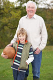 Grandfather With Grandson Holding Football Stock Photos