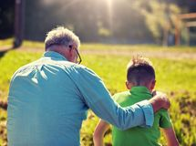 Grandfather and grandson hugging outdoors stock images