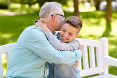 Grandfather and grandson hugging at summer park Royalty Free Stock Images