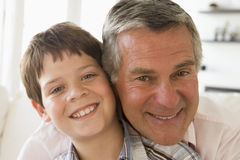 Grandfather and grandson indoors smiling Royalty Free Stock Image