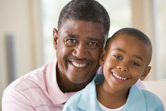 Grandfather and grandson indoors smiling.  Royalty Free Stock Photos