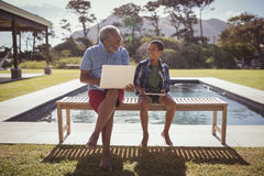 Grandfather and grandson interacting with each other near swimming pool Stock Image