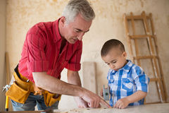 Grandfather and grandson knocking a nail with a hammer in a carp Stock Images