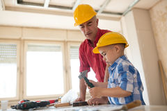 Grandfather and grandson knocking a nail with a hammer in a carp Royalty Free Stock Images