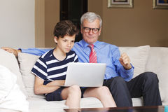 Grandfather and grandson with laptop Royalty Free Stock Photography