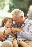 Grandfather With Grandson Laughing Together On Sofa Stock Images