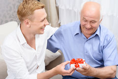 Grandfather and grandson with little present Stock Images