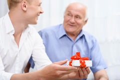 Grandfather and grandson with little present Stock Image