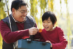 Grandfather and grandson looking at fishing tackle box Stock Photo
