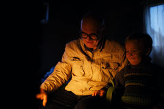 Grandfather and grandson near fire at home. Stock Photography